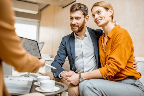 Young couple choosing house at the real estate agency